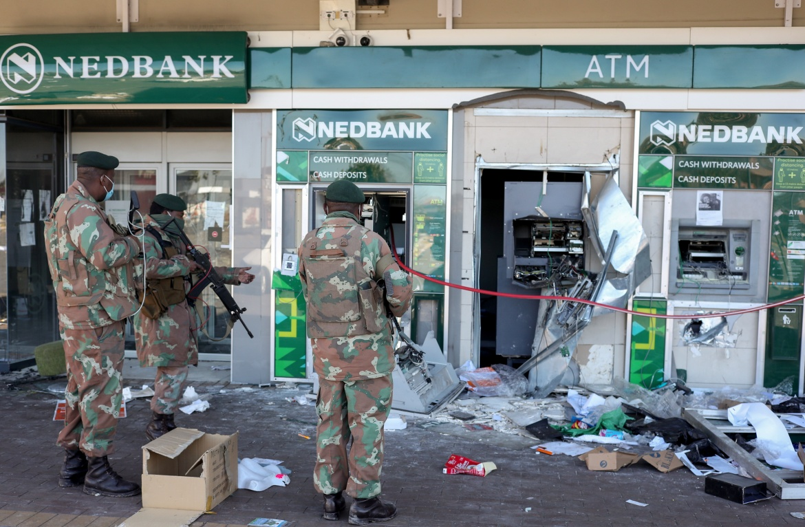 Members of the military look at the damaged ATMs outside a bank in Soweto as the country deploys the army to quell unrest linked to the jailing of former President Jacob Zuma. [Siphiwe Sibeko/Reuters]