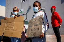 People stand with placards as President Ramaphosa visits a shopping centre that was damaged after several days of looting in Durban [File: Rogan Ward/Reuters]