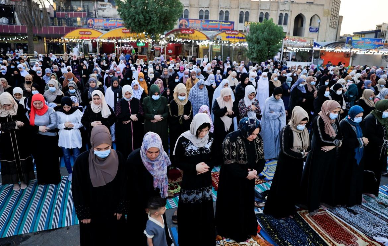 Iraqi Muslims offer Eid al-Adha prayers on the street outside the Abu Hanifa mosque in Baghdad's Adhamiya district. [Thaier Al-Sudani/Reuters]