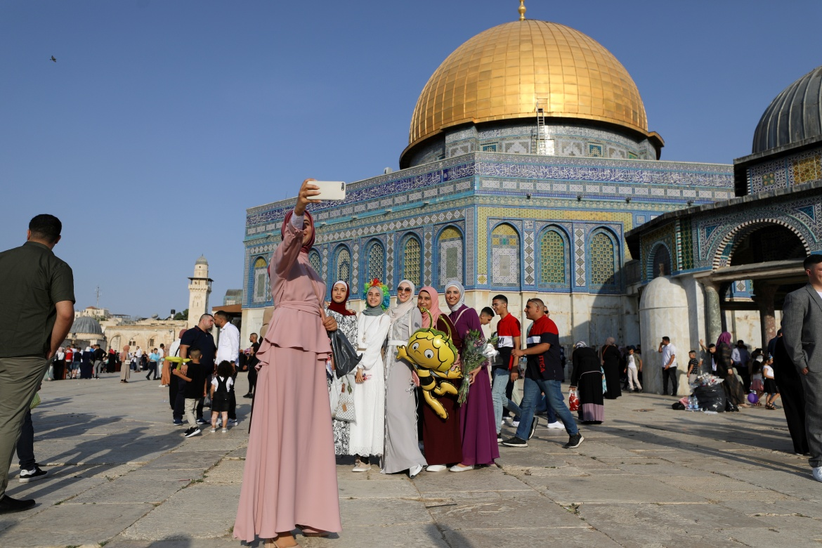 Palestinian women pose for a picture by the Al-Aqsa Mosque as they mark the first day of the Muslim holiday of Eid al-Adha. [Ammar Awad/Reuters]