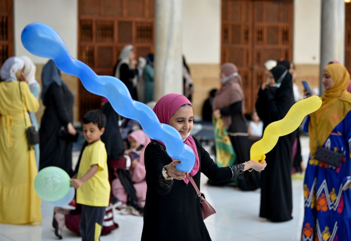 Kids play with balloons after Eid al-Adha prayers inside al-Azhar Mosque in Cairo, Egypt. [Mohamed Abd El Ghany/Reuters]