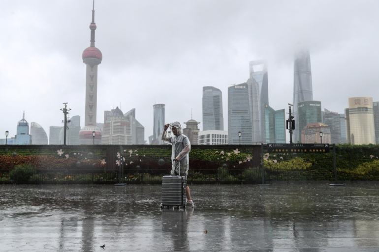A man with luggage walks in the rain on The Bund as Typhoon In-fa approaches Shanghai [cnsphoto via Reuters]