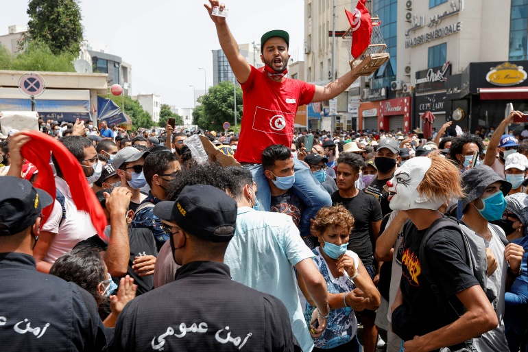 Demonstrators gather in front of police officers during an anti-government protest in Tunis, July 25, 2021 [Zoubeir Souissi/ Reuters]
