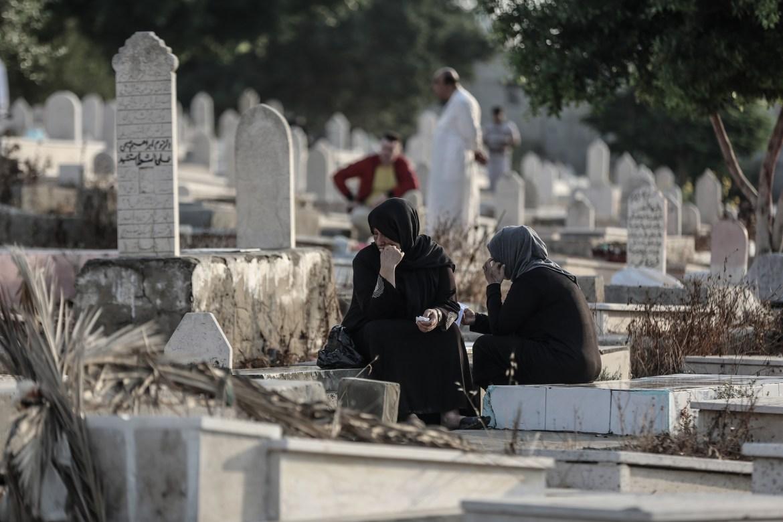 Palestinians visit a cemetery in Gaza City to offer prayers to their relatives on Eid al-Adha. [Ali Jadallah/Anadolu]