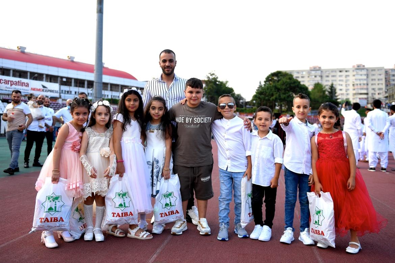 People pose for a photo after performing Eid al-Adha prayers at the Dinamo Stadium in Bucharest, Romania. [Alex Nicodim/Anadolu]