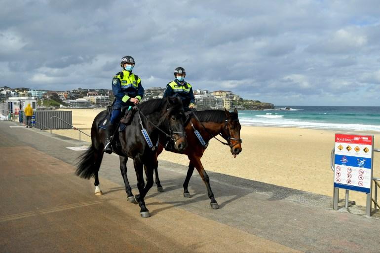 Patroli polisi yang dipasang di Pantai Bondi di Sydney  Pembatasan virus corona diperketat pada hari Jumat setelah lonjakan kasus File Joel Carrett/AAP Image via AP Photo