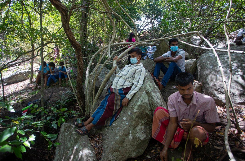 Sri Lankan parents rest lying on rock boulders as their children follow online lessons at a mobile signal reception point on a mountain top in Bohitiyawa village. [Eranga Jayawardena/AP Photo]