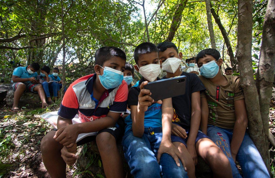 Children share a smartphone to receive their online lessons on a mountain top in Bohitiyawa village. [Eranga Jayawardena/AP Photo]
