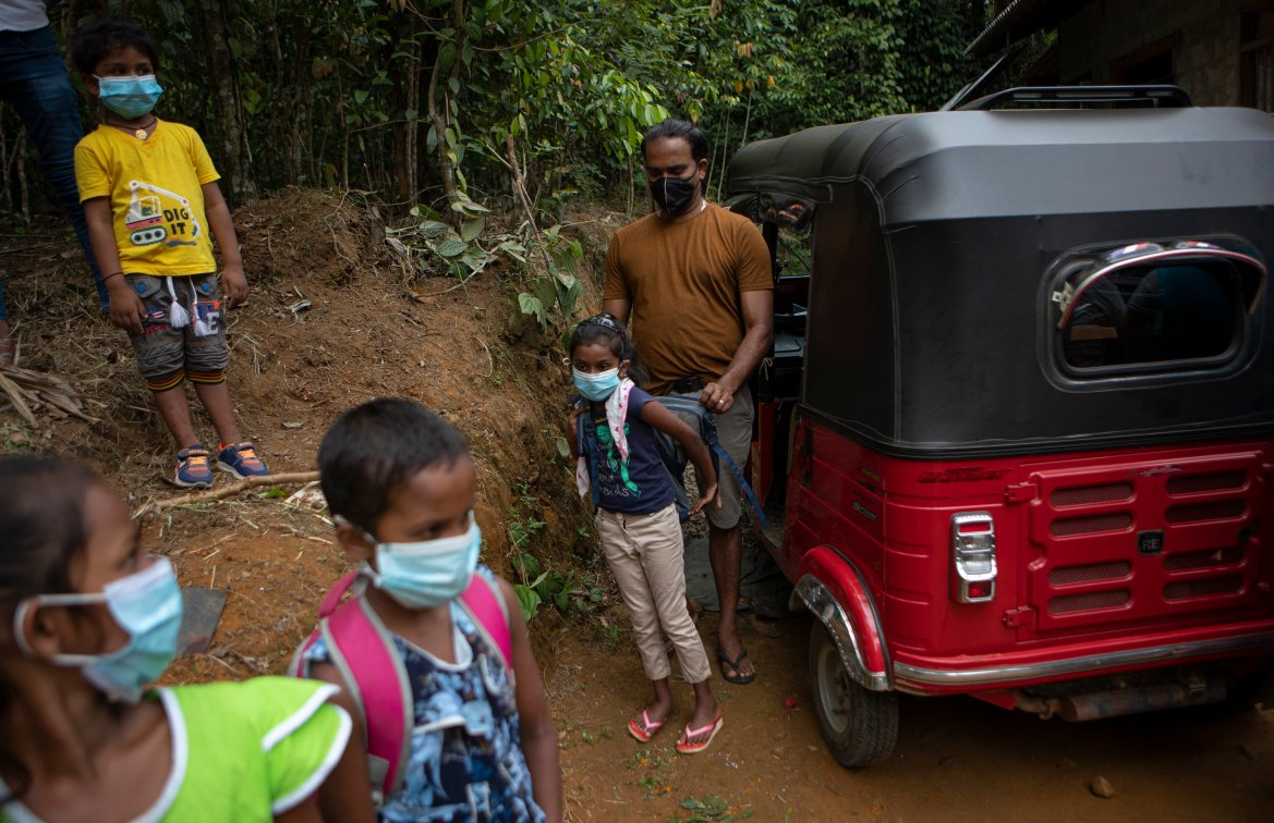 A Sri Lankan man helps his son put his bag on his back as they prepare to climb a mountain with others to access online lessons. [Eranga Jayawardena/AP Photo]