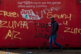 """A man walks past graffiti reading """"free Zuma"""" and """"we want Zuma"""" outside a shopping mall in Vosloorus, east of Johannesburg, South Africa, on Wednesday, July 14, 2021 [AP Photo/Themba Hadebe]"""
