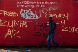 A man walks past graffiti reading