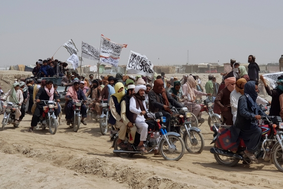 Supporters of the Taliban carry their signature white flags after they seized the Afghan border town of Spin Boldak [File: Tariq Achkzai/AP Photo]