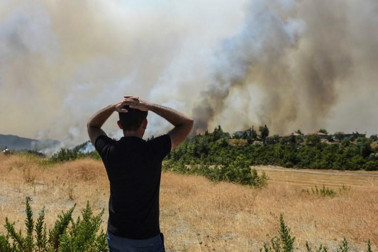 A man watches wildfires in Kacarlar village near the Mediterranean coastal town of Manavgat, Antalya, Turkey, on Saturday, July 31, 2021 [AP Photo]