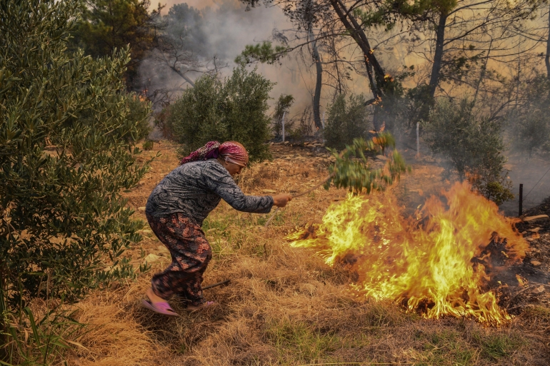 A woman tries to stop an advancing wildfire in Kacarlar village near the Mediterranean coastal town of Manavgat, Antalya, Turkey, Saturday, July 31, 2021 [AP]