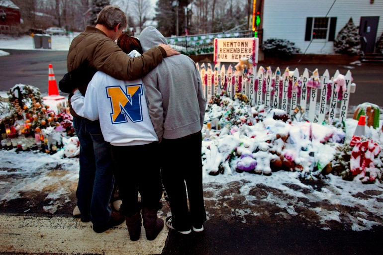 A family stands near memorials by the Sandy Hook firehouse in 2012 in Newtown, Connecticut, the United States [File: Craig Ruttle/AP]