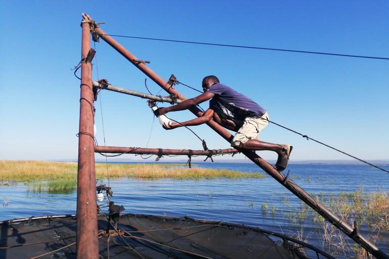 Takuchinchi Munsaka, from Muyobe village in Binga, makes final preparations before going fishing along the Zambezi River [Farai Matiashe/Al Jazeera]