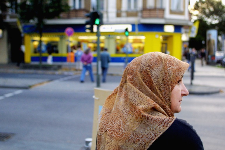 A Muslim woman waits to cross a street in Berlin's Neukoelln district. [File: Sean Gallup/Getty Images]