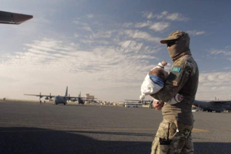 A Kazakh military officer is seen as he carries a child during the Zhusan humanitarian operation in 2019. [Astana Times]