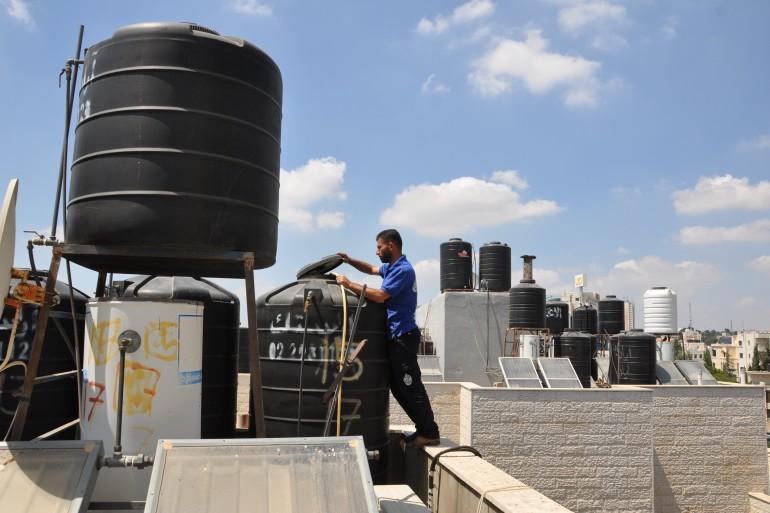 Superintendent Bassam Rayan fills residents' private water tanks at the Khawaja apartment building in Ramallah [Mohammed Najib/Al Jazeera]