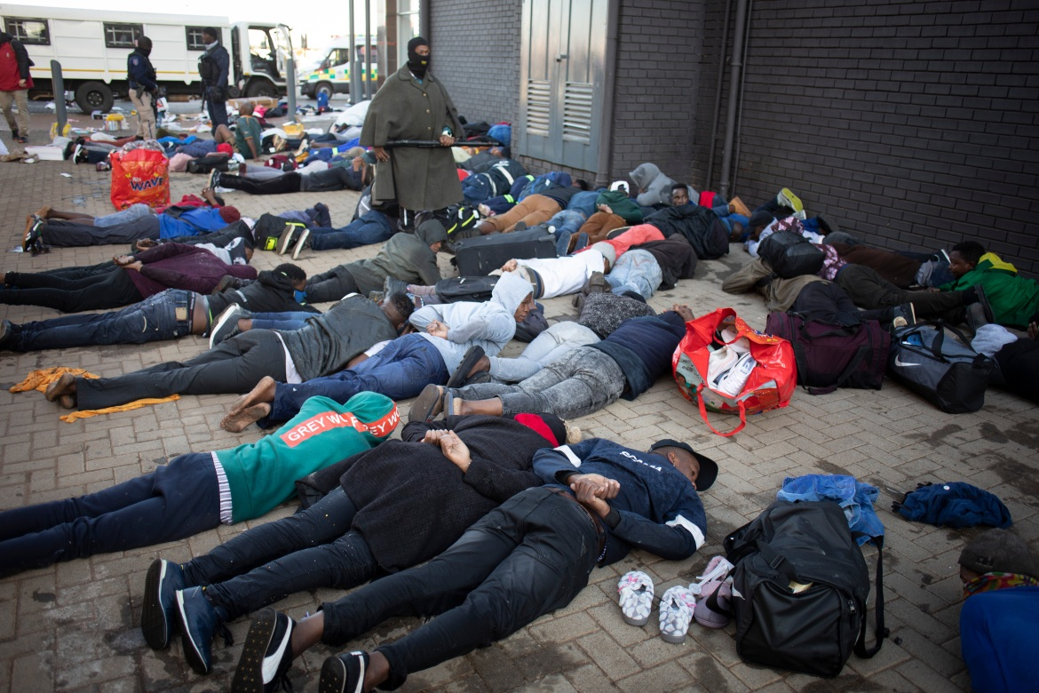 Arrested looters lie on the ground after being arrested in Johannesburg. [Kim Ludbrook/EPA]