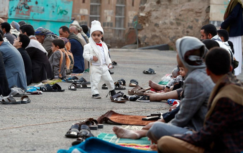 A child stands among people attending Eid al-Adha prayers in Sanaa, Yemen. [Yahya Arhab/EPA]