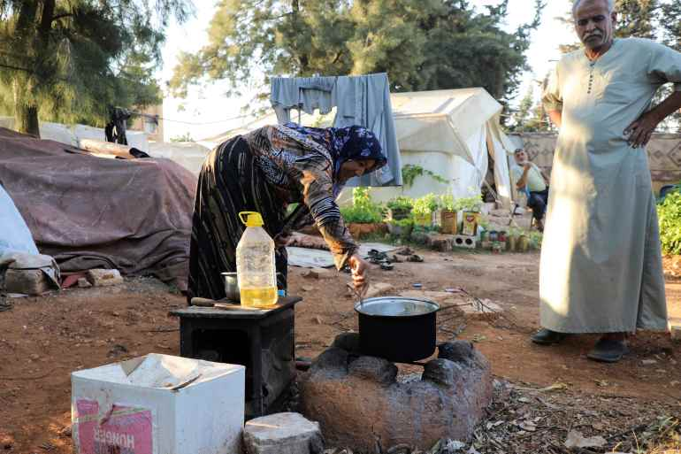 Seorang wanita memasak makanan di sebuah kamp untuk pengungsi internal di Suriah, di mana harga minyak goreng telah melonjak 440 persen dibandingkan tahun lalu, menurut PBB File Mahmoud Hassano/Reuters