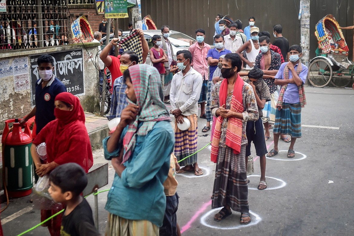 People waiting in a queue for the food distributed by Mehmankhana, which feeds hundreds of unemployed or struggling workers. [Munir Uz zaman / AFP]