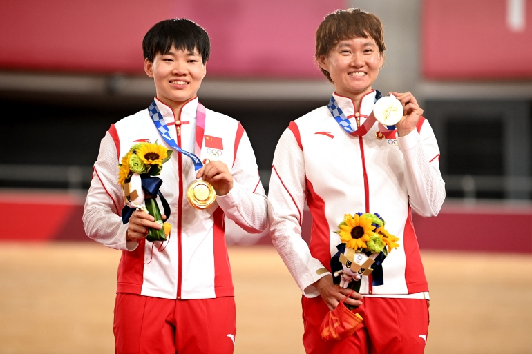 Gold medallists Bao Shanju, left, and Zhong Tianshi of China wore badges of the late Chinese chairman Mao Zedong on the podium [Matthew Childs/Reuters]