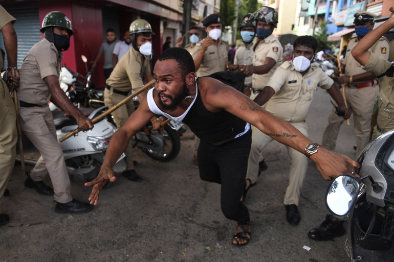 Police baton charge a man protesting the death of the African national in Bengaluru city [AFP]