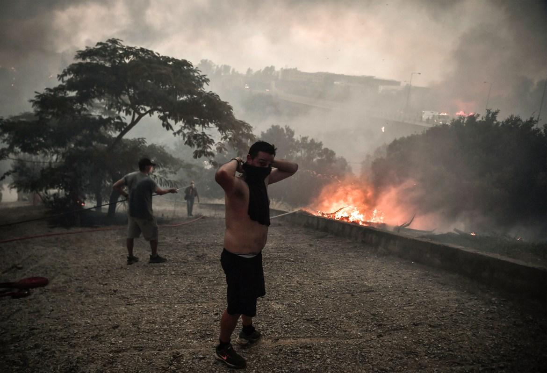 Locals fight against a fire in Tatoi forest near Acharnes. [Louisa Gouliamaki/AFP]