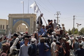 Taliban fighters stand on a vehicle along the roadside in Kandahar, Afghanistan [AFP]