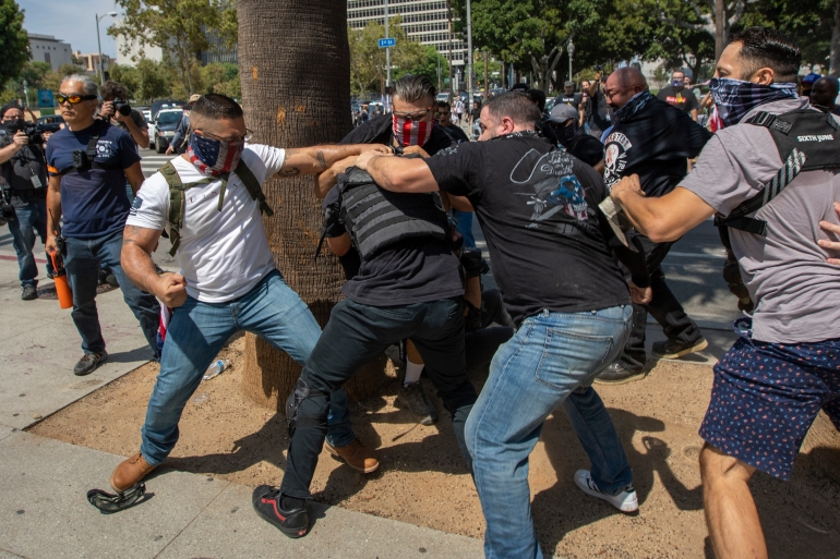Anti-vaccination protesters beat up a counter-demonstrator during an anti-vaccination rally near LA City Hall [David McNew/AFP]