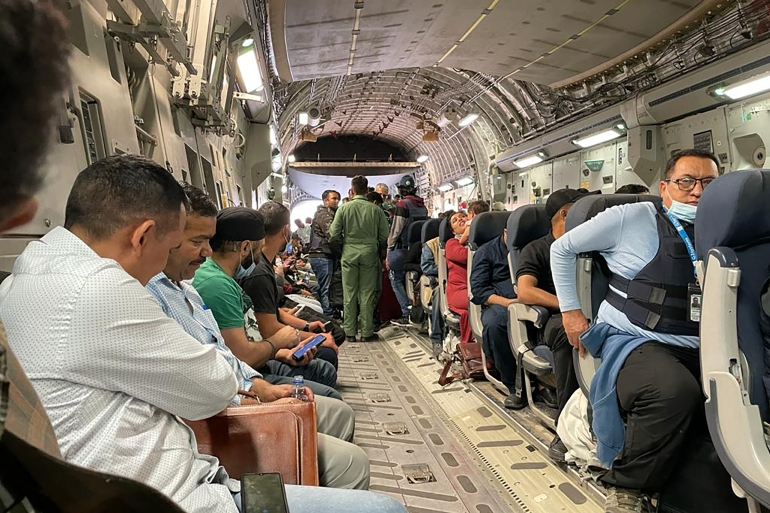 Indian nationals sit on board an Indian military aircraft at the airport in Kabul [AFP]