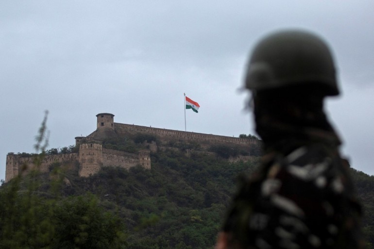 In this photo taken on August 15, 2021, an Indian soldier stands guard as India's national flag flutters on Hari Parbat Fort in Srinagar to mark India's 75th Independence Day [File: Abid Bhat/AFP]