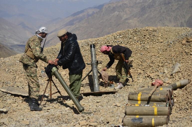 Pessoal da Frente de Resistência Nacional instala armas pesadas em um posto avançado no distrito de Paryan, na província de Panjshir, no mês passado [Ahmad Sahel Arman/AFP]