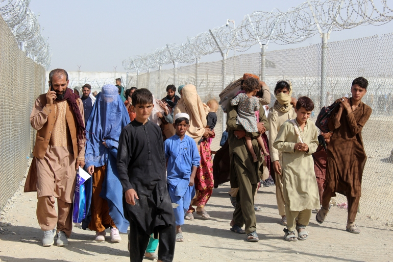 Afghans walk through a fenced corridor to enter Pakistan at the Pakistan-Afghanistan border crossing in Chaman [AFP]