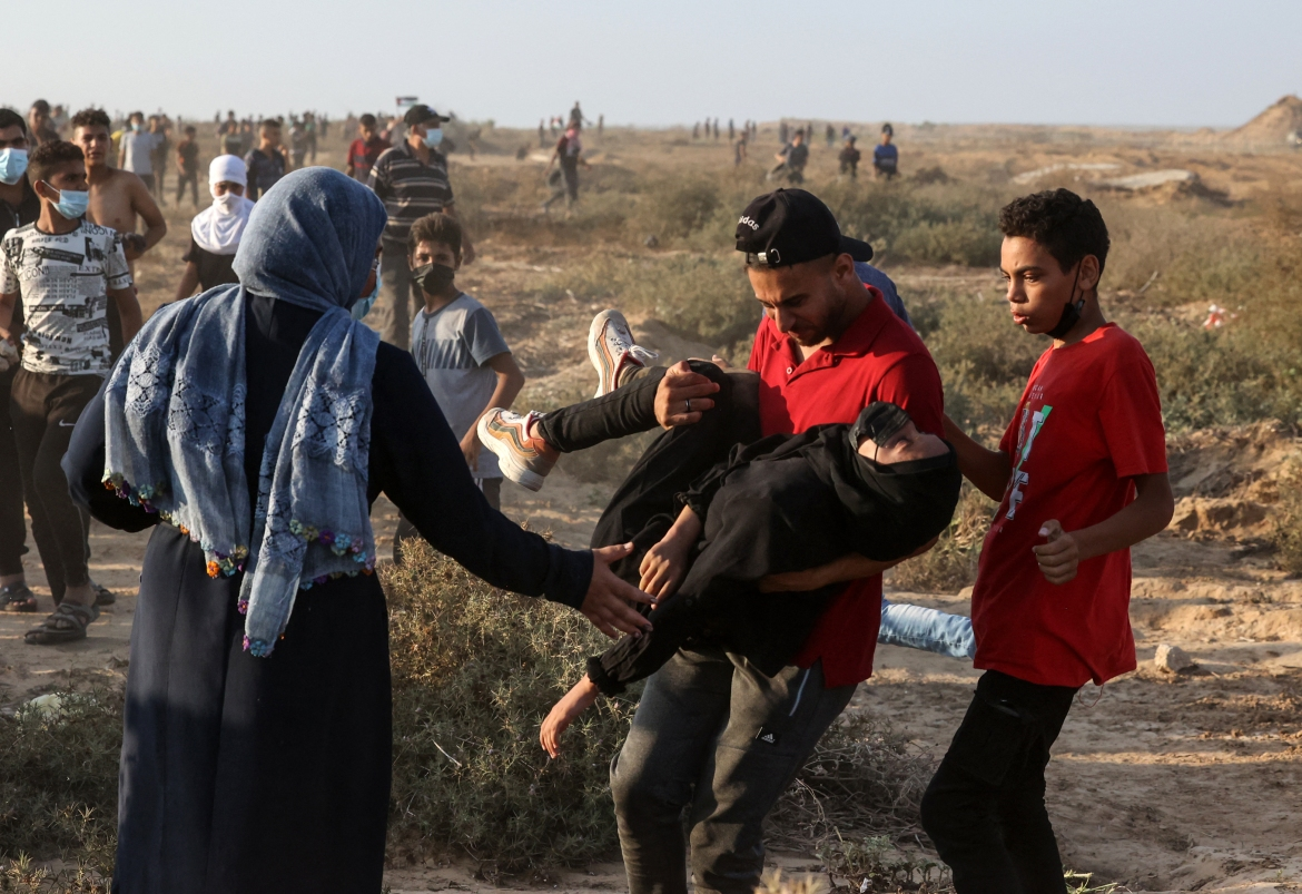 A Palestinian demonstrator carries an injured woman away from Israeli security forces following a protest along the separation barrier. [Mahmud Hams/AFP]