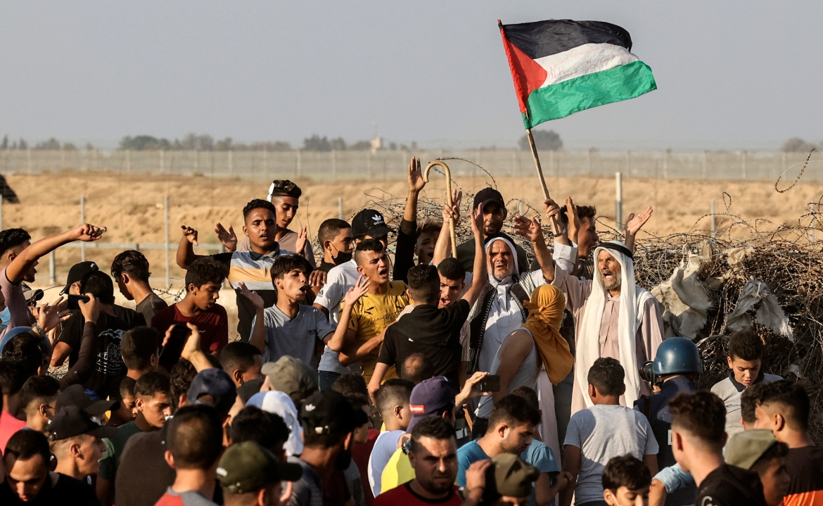 A Palestinian demonstrator raises a national flag during the protest along the separation barrier in the southern Gaza Strip. [Mahmud Hams/AFP]