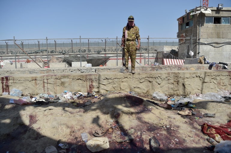A Taliban fighter stands guard at the site of the August 26 suicide bomb, which killed at least 175 people, including 13 US troops, at Kabul airport [Wakil Kohsar/AFP]