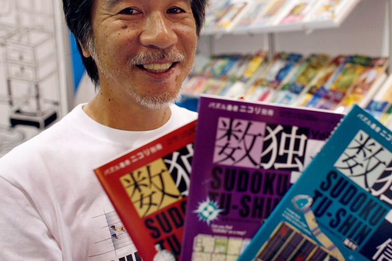 'Godfather of Sudoku' Maki Kaji holds copies of the latest sudoku puzzles at the Book Expo, in New York, June 3, 2007. [File: Chip East/Reuters]