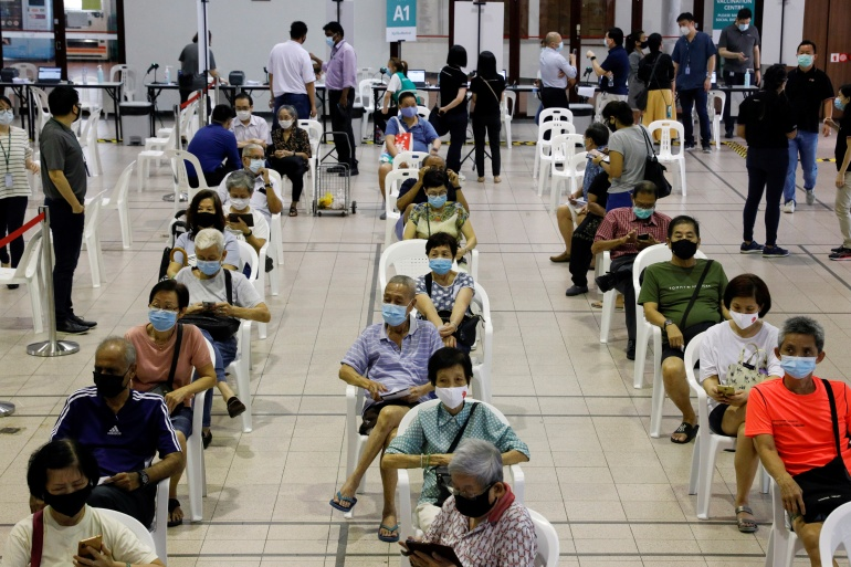 People older than 70 wait in an observation area after getting a COVID-19 jab at a vaccination centre in Singapore [File: Edgar Su/ Reuters]