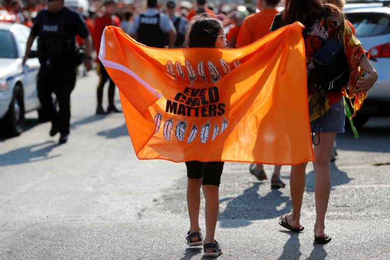 A child holds a flag that reads 'Every Child Matters' during a march in British Columbia after the discovery of hundreds of unmarked graves of Indigenous children at residential schools across Canada [File: Kevin Light/Reuters]