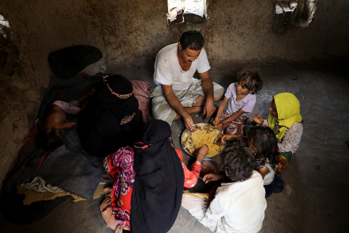 Ali al-Emadi, who works as a lumberjack, eats lunch with his family. 'If I get something, we eat. At least we live or die together.' [Khaled Abdullah/Reuters]
