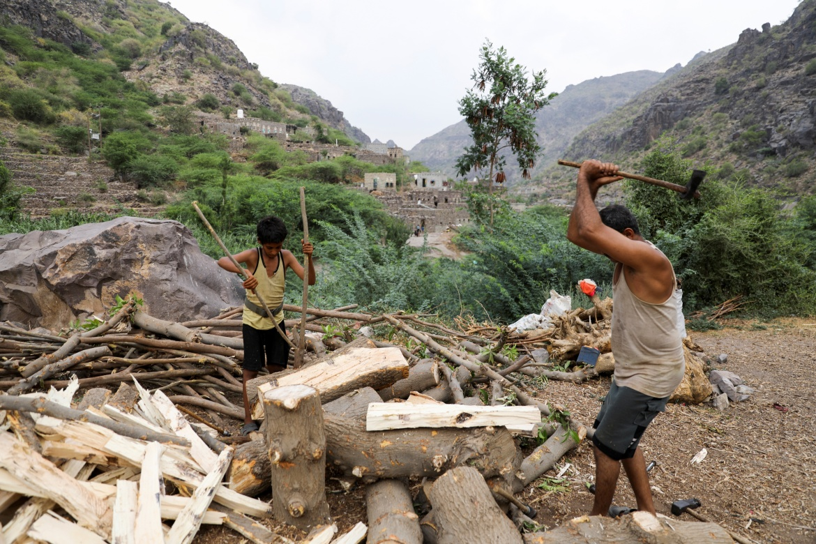 Ali al-Emadi, who works as a lumberjack, and his nephew split firewood with axes at their village in Khamis Banisaad district of al-Mahweet province. [Khaled Abdullah/Reuters]