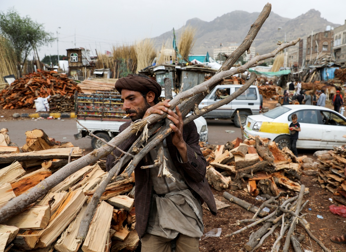 A vendor carries wood at a firewood market in Sanaa. [Khaled Abdullah/Reuters]