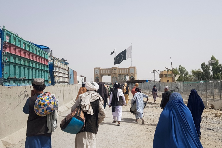 People arriving from Afghanistan make their way at the Friendship Gate crossing point at the Pakistan-Afghanistan border town of Chaman [Abdul Khaliq Achakzai/Reuters]