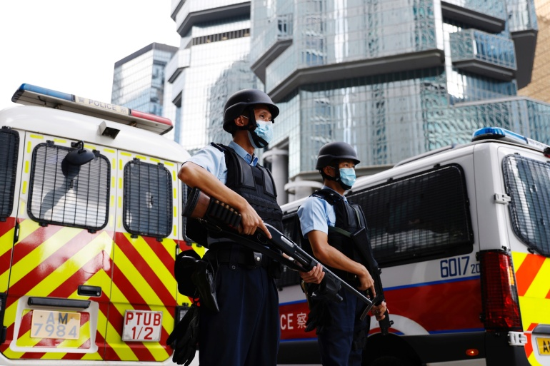 Armed police were deployed as Andy Li and Chan Tsz-wah were brought to court [Tyrone Siu/Reuters]
