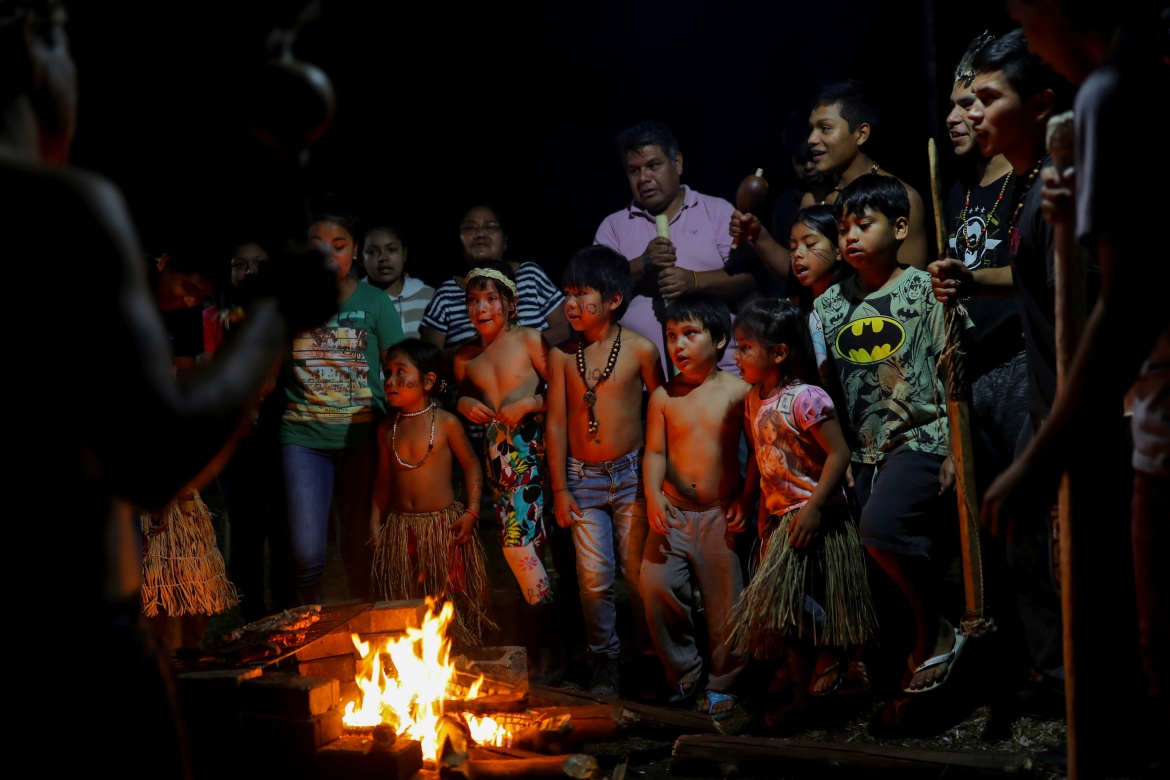 Determined to keep their traditions alive, the Xokleng gather around bonfires at night to tell stories in their own language and keep up their rituals of dance and prayer, sometimes painting the faces of their young ones. [Amanda Perobelli/Reuters]