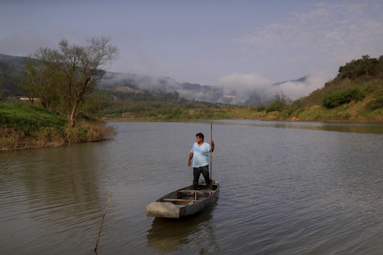 Lazaro Kamlem, 47, 'cacique' of Palmeira village, stands in a wood canoe in Itajai river in Xokleng Laklano Indigenous land, Jose Boiteux, Santa Catarina state, Brazil. [Amanda Perobelli/Reuters]
