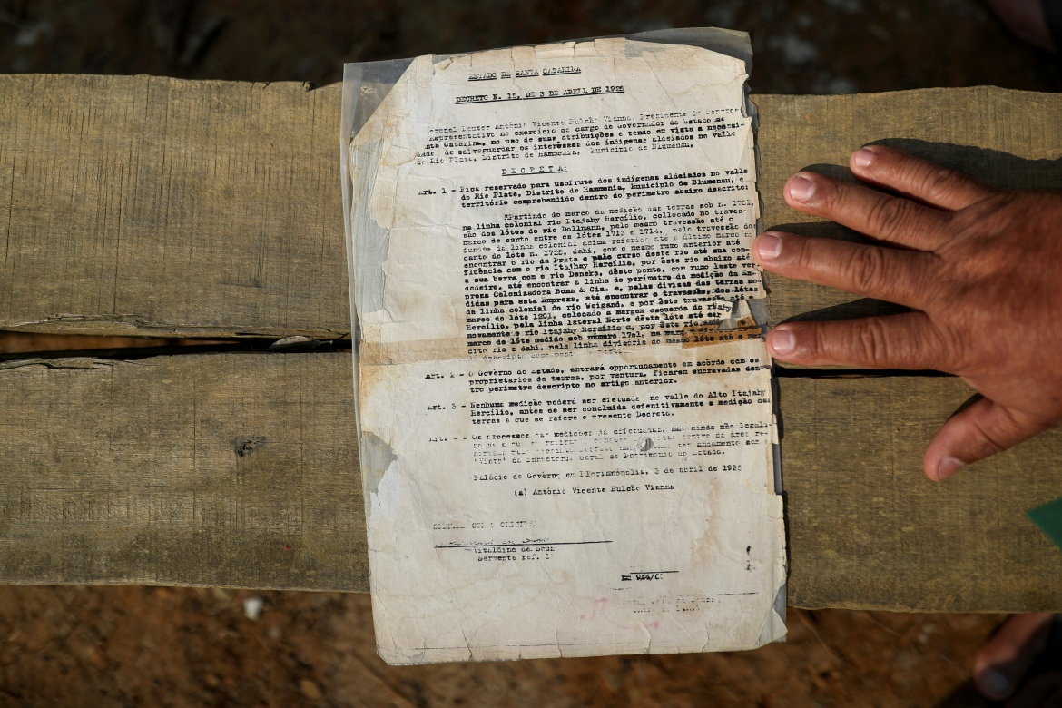 Community leader Brasilio Pripra, 63, shows the document issued by Santa Catarina state office about Indigenous land in the region in Xokleng Laklano Indigenous land. [Amanda Perobelli/Reuters]